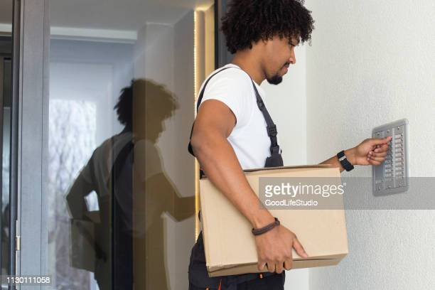 young african man delivering a package - intercom stock pictures, royalty-free photos & images