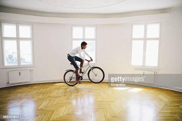 young african man drive his bicycle in unfurnished loft apartment