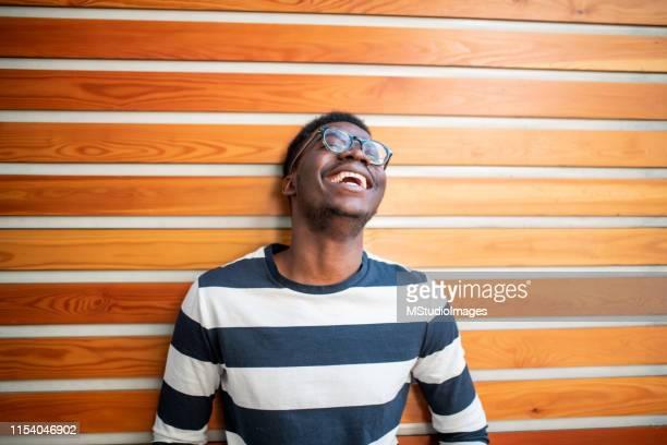 young african man laughing. - só homens jovens imagens e fotografias de stock