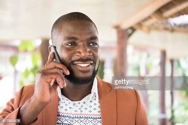 Young African man on cell phone, looking away smiling