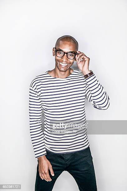 A young african man posing in a studio looking happy