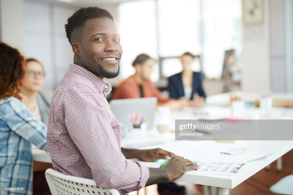 Young African Man Posing in Office : Stock Photo