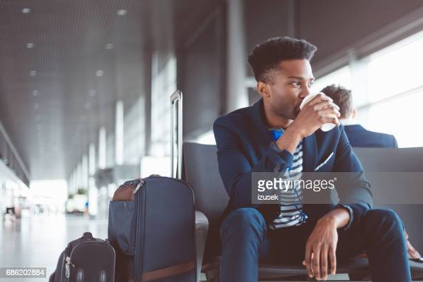 Young african man sitting at waiting area in airport