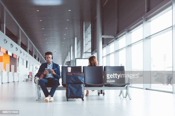 Young african man using digital tablet at airport lounge