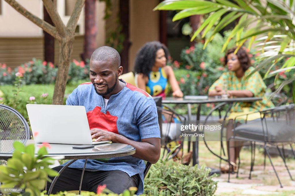 Young African man using laptop in cafe garden using : Stock Photo