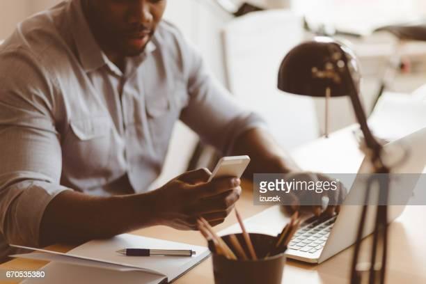 Junge afrikanische Mann mit Handy während der Arbeit