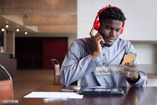 young african man using tablet in cafe - on the move stock pictures, royalty-free photos & images