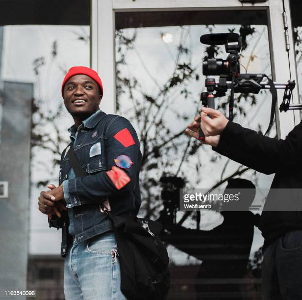 young african man wearing a red hat and denim jacket and hat outdoors - webfluential stock pictures, royalty-free photos & images