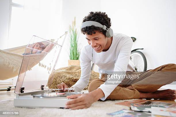 young african man with big earphones and record player