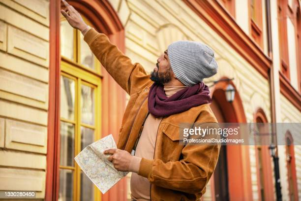 young african man with tourist map is enjoying walking in the city district. - individual event stock pictures, royalty-free photos & images