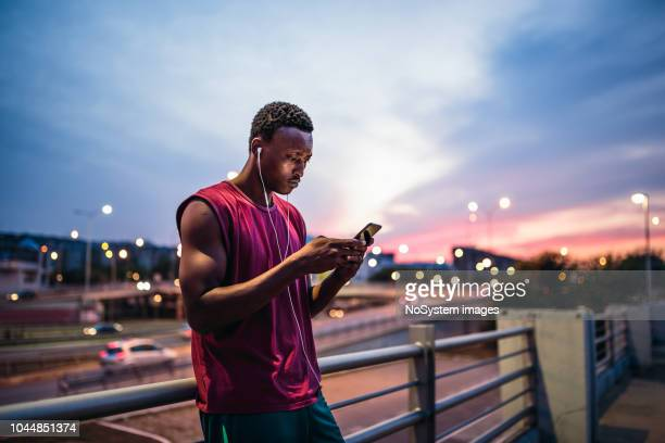 young african men resting after training outdoors, using mobile phone - city life stock pictures, royalty-free photos & images