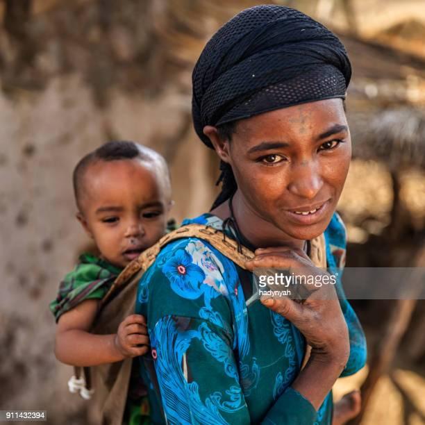 jonge afrikaanse moeder met haar baby op rug, oost-afrika - dorp stockfoto's en -beelden