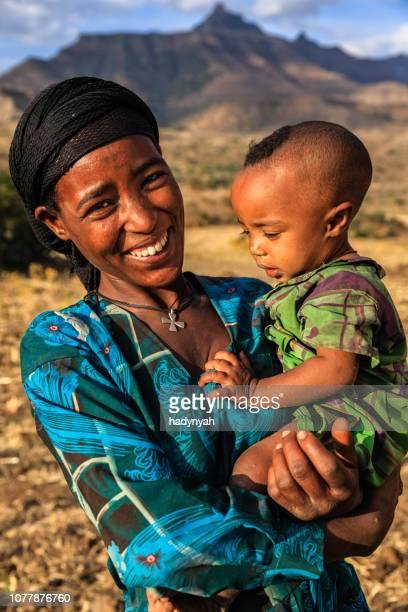東アフリカの彼女の赤ん坊を保持している若いアフリカの母 - horn of africa ストックフォトと画像