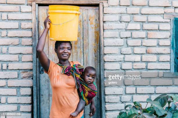 young african mother with baby carrying water bucket on head - carrying stock pictures, royalty-free photos & images