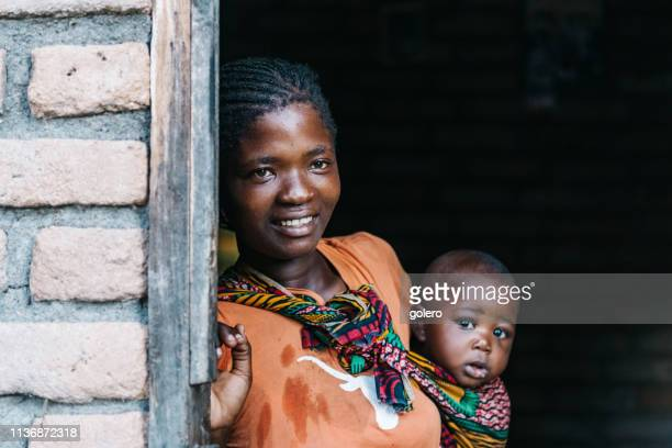 young african mother with baby standing in the door