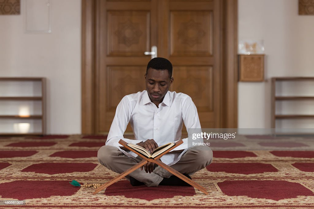 Young African Muslim Guy Reading The Koran : Stock Photo