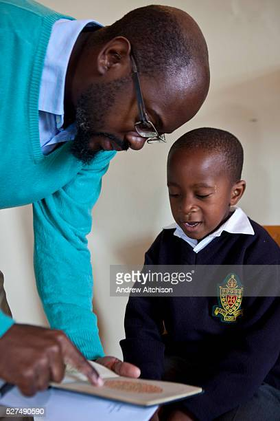 A young African school boy reads green numbers that he can read on an orange plate in a book shown to him by a male optician in a classroom in...
