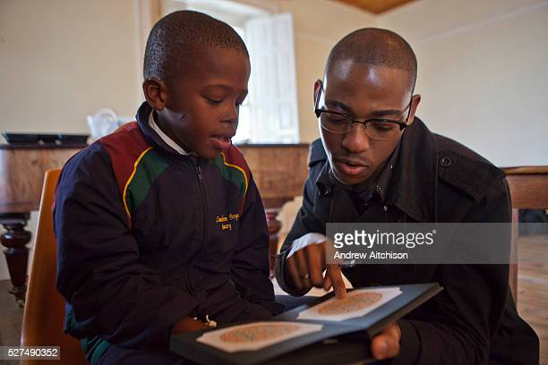 A young African school child reads green numbers that he can read on an orange plate from a black book shown to him by a male optician in a class...