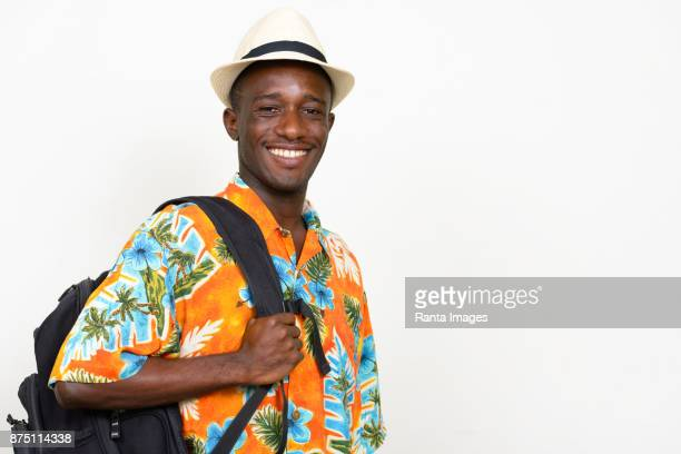 young african tourist man wearing hat and hawaiian shirt against white background - hawaiian shirt stock photos and pictures