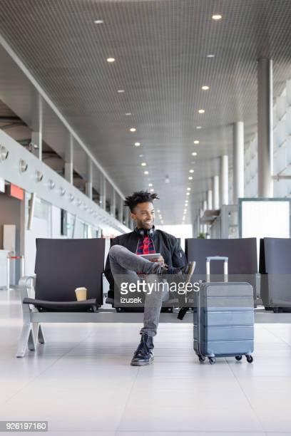 young african using digital tablet in airport lounge - izusek imagens e fotografias de stock