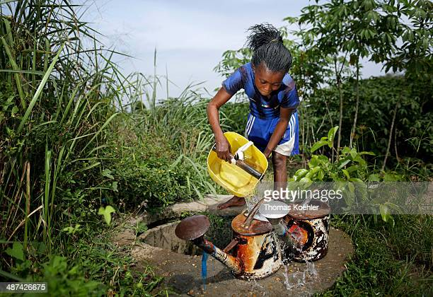 A young African woman at work in the fields filling watering cans to water crops just outside Bangui pictured on March 13 2014 near Bangui Central...