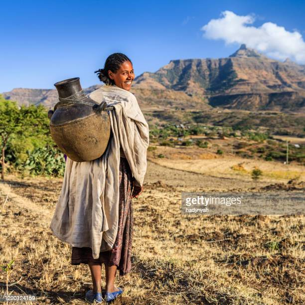 young african woman carring jug of water, ethiopia, africa - ethiopia stock pictures, royalty-free photos & images