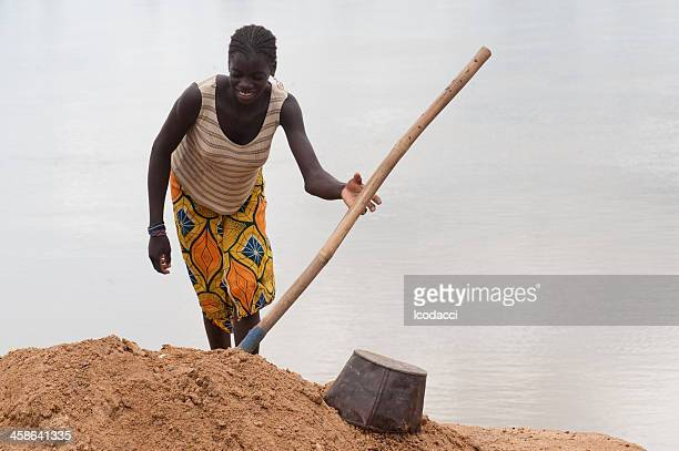 Young african woman digging on a riverside