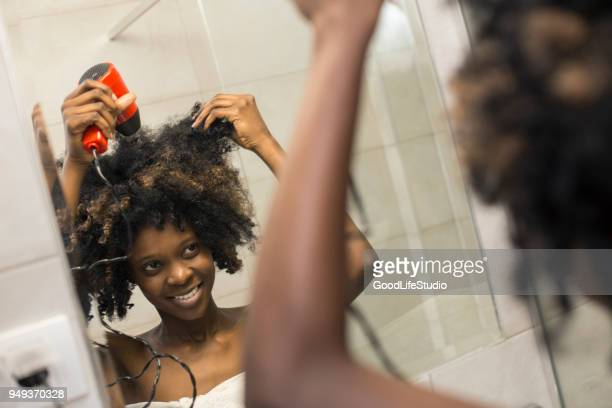 young african woman drying her hair - blow drying hair stock pictures, royalty-free photos & images