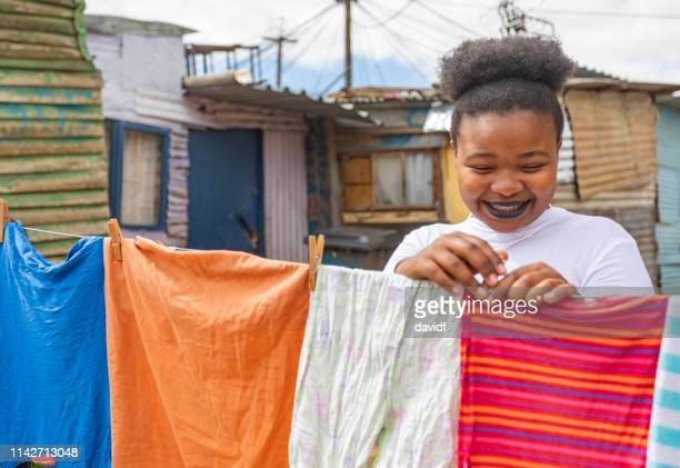 jonge afrikaanse vrouw opknoping uit kleren - gemeente stockfoto's en -beelden