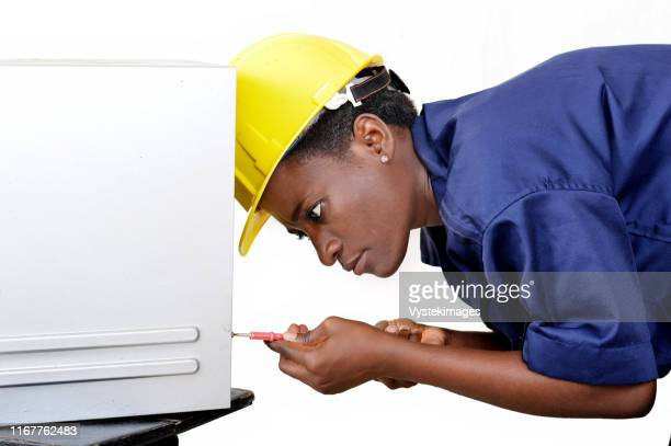 young african woman in computer maintenance opens the central unit with a turning - côte d'ivoire stock-fotos und bilder