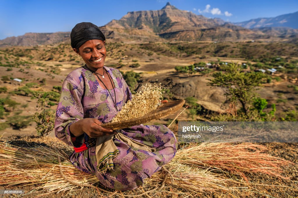 Young African woman is sifting the sorghum, East Africa : Stock Photo