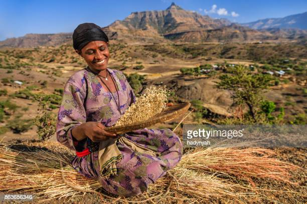 Young African woman is sifting the sorghum, East Africa