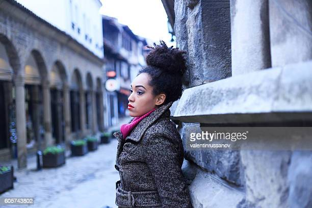 Young african woman leaning on stone wall on street