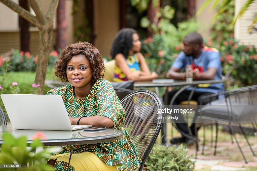 Young African woman looking to camera using laptop : Stock Photo