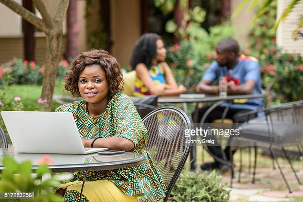 Young African woman looking to camera using laptop