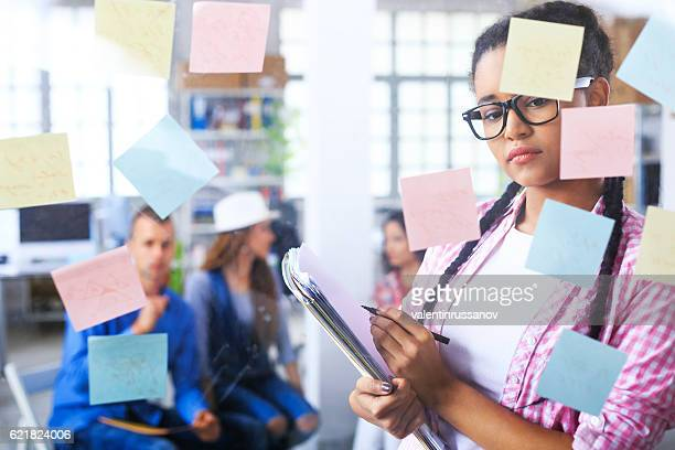 Young african woman reading post-it notes on glass wall