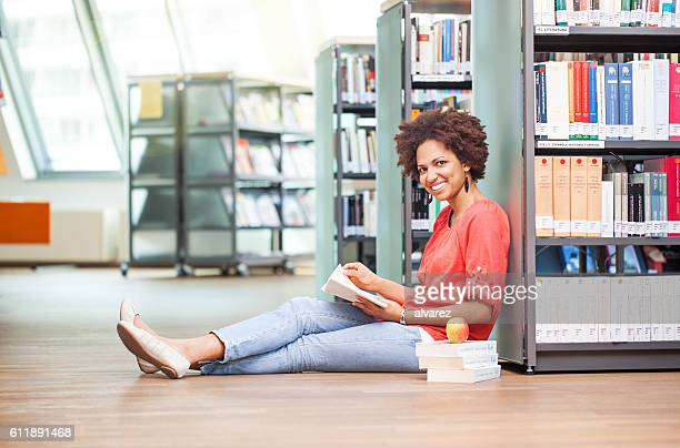 Young african woman sitting on floor in library