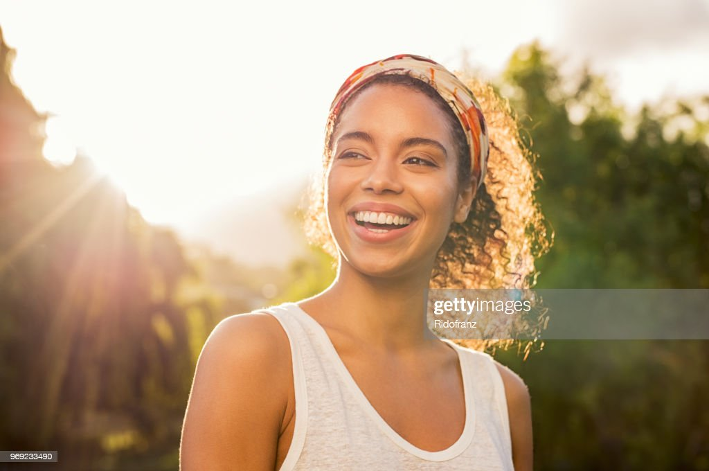 Young african woman smiling at sunset : Stock Photo