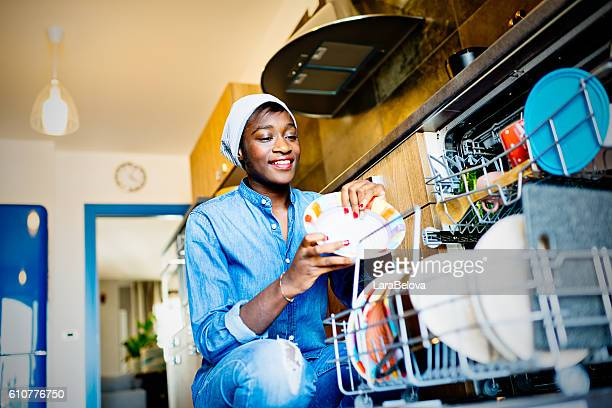 Young African woman using dishwasher in domestic kitchen