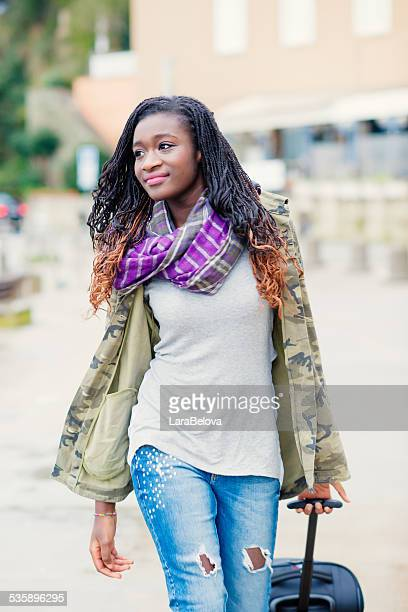 Young African woman walking on the street with trolley