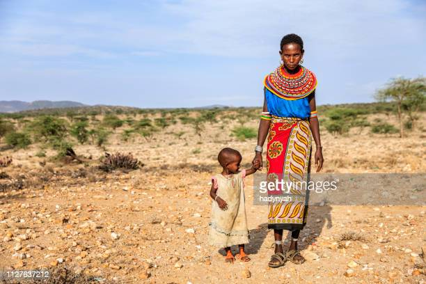 young african woman walking with her baby, kenya, east africa - african tribal culture stock pictures, royalty-free photos & images
