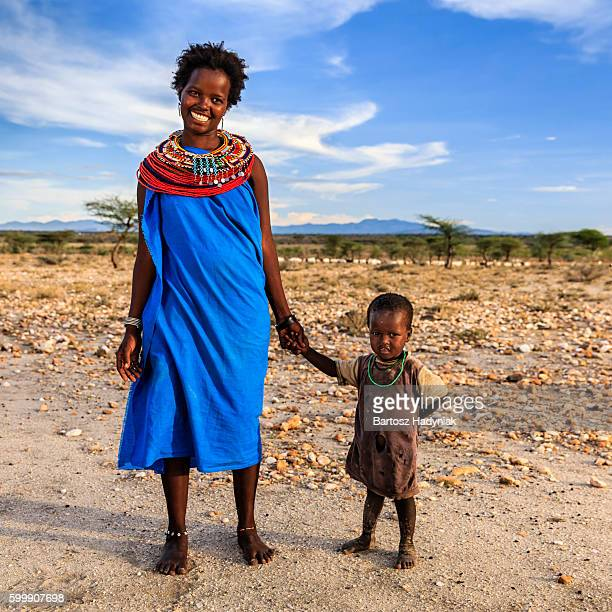 young african woman walking with her baby, kenya, east africa - 民族衣装 ストックフォトと画像