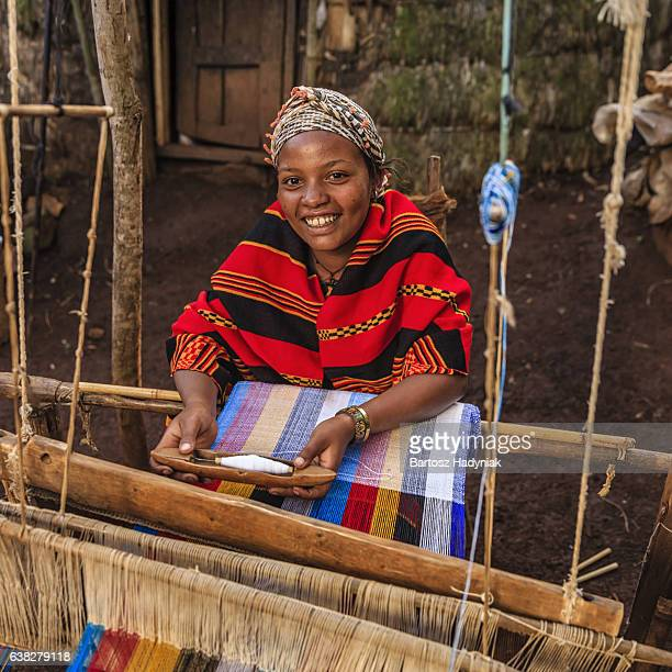 Young African woman weaving a colorful scarf, Ethiopia, East Africa