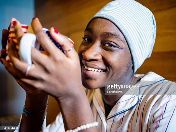 Young African woman with mug at morning