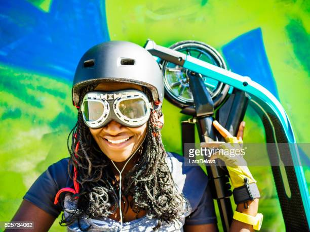 Young African woman with scooter, graffiti on background