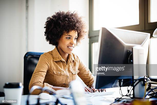 Young African Woman Working in Loft Space Behind Computer