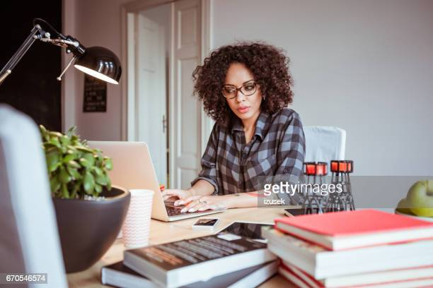 Young african woman working on laptop in office