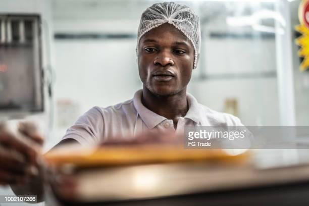 肉の重量を量る肉屋で働くアフリカ系の若者 - 食料倉庫 ストックフォトと画像