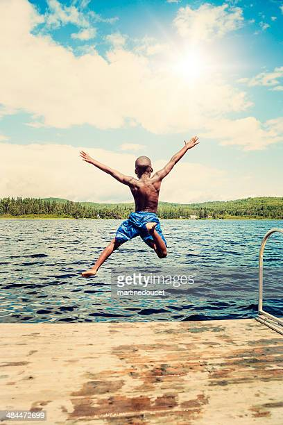 Young african-american boy jumping from a pier in lake.