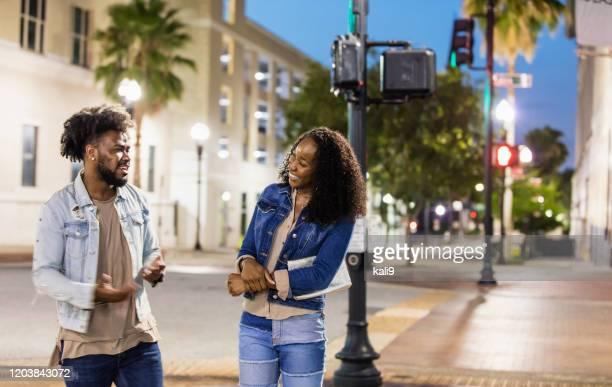 giovane coppia afroamericana che attraversa city street - afro americano foto e immagini stock